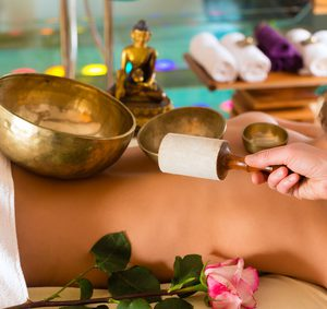 Woman in wellness and spa setting having a singing bowl massage therapy
