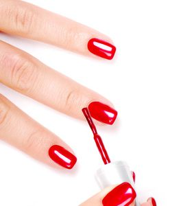 Manicurist applying red nail polish on female fingers.